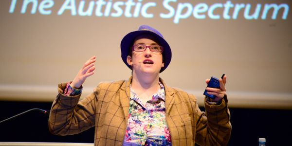 `photo of Robyn wearing-a. purple-hat giving a lecture.