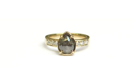 Pear shaped grey diamond with round brilliant cut white diamond engagement ring.