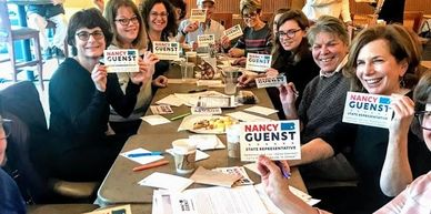 A photo of a group of people placing hand-written messages on campaign postcards