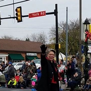 This is a photo of Nancy smiling and waving while walking in a holiday parade in Hatboro, PA.