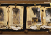 Exodus: burnt book pages, burnt sheet music, printed images, keys, dried seed pods, straw, sandpaper, wooden frame, rusted washers