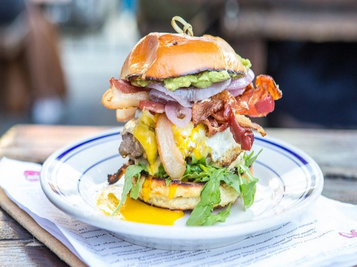 The Proper Burger® at Duke's Grocery. Shown with Applewood Smoked Bacon, Smashed Avocado & Runny Egg