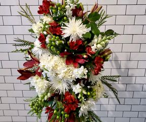 A red and white funeral spray stand