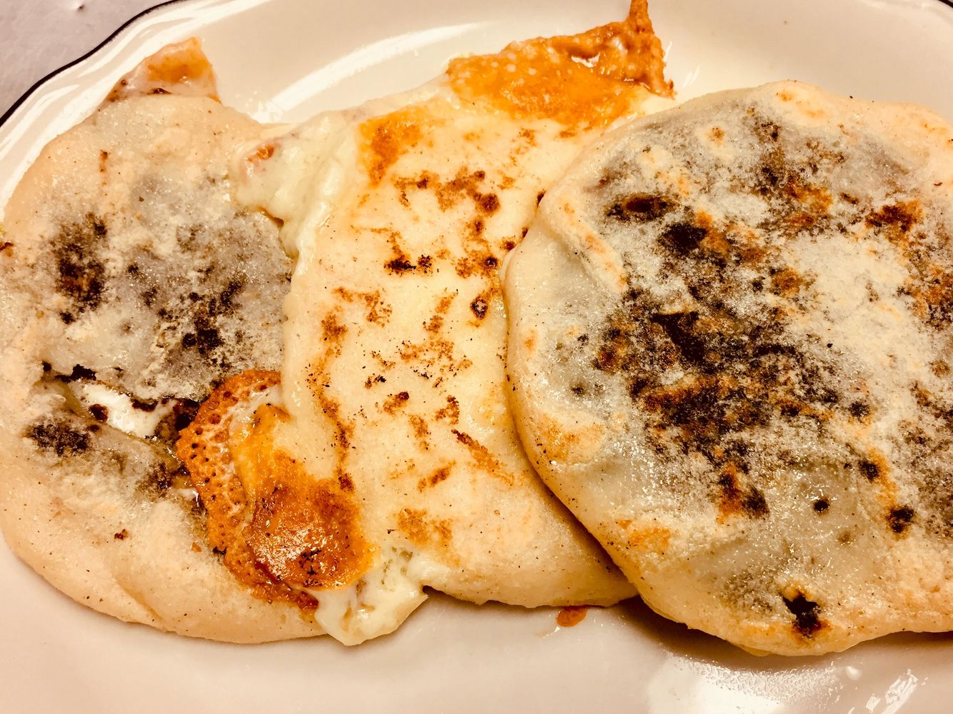 Three round, overlapping pupusas on a plate. The middle pupusa has crispy cheese edges.