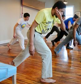 Students practice the basic movement, ginga, in a class