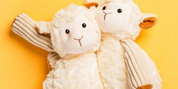 yellow background stuffed animals hugging lamb sheep