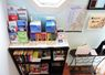 Bookshelf at base of stairs has various reading and activity books as well as tourism information brochures, maps, book, and guest book. Binoculars