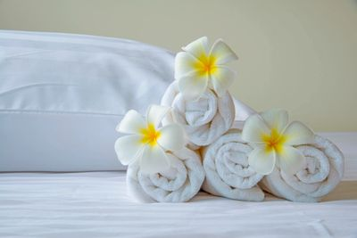towels rolled up on bed with flowers