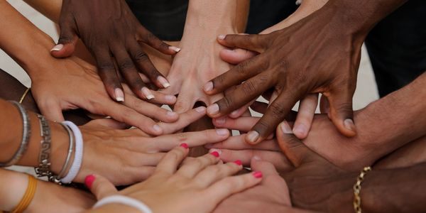 Multicultural group of extended hands