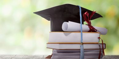 Textbooks with mortarboard and diploma
