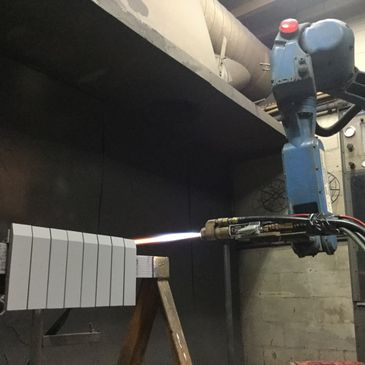 Robot being used with HVOF to protective coat plates