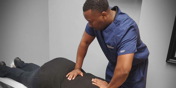 Chiropractor assessing muscle tension and sprain strain injury