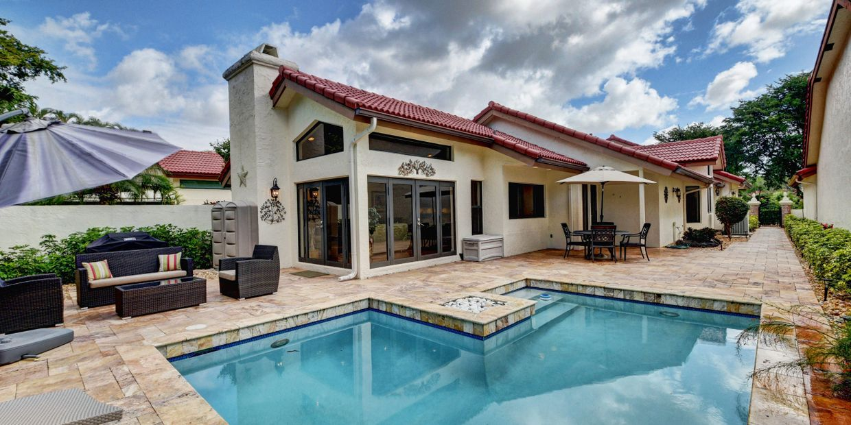 Courtyard home showing the beautiful pool with travertine and glass doors to the living room.