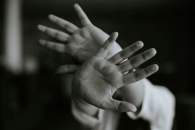 Persons hands shielding them from perceived danger.