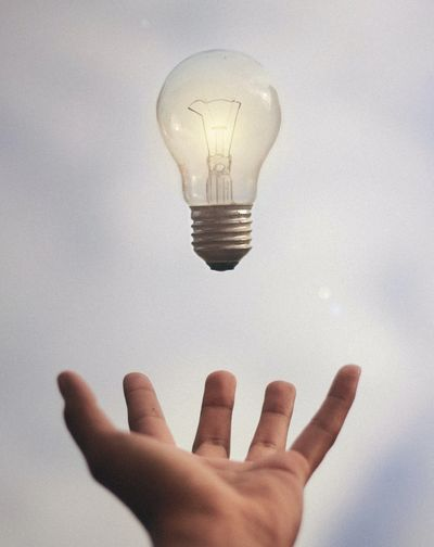 A lightbulb hovering over an open hand