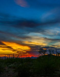 Photo of sunset with blues, bright red and yellow in Tucson Mountains with desert foreground