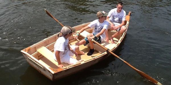 Campers paddling a wooden skiff
