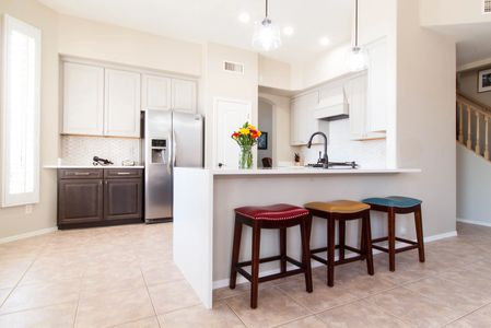 Colorful chairs at white waterfall counter in kitchen remodel in mesa