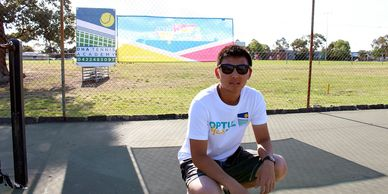 Tennis coach Darren Ha from DHA Tennis Academy in St Albans kneeling down on tennis court