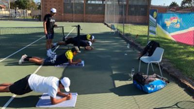 Tennis coach standing while four elite tennis players are on ground doing core strengthening