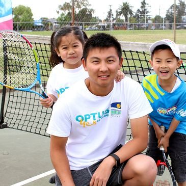 Young girl holding tennis racquet with young boy and tennis coach from DHA Tennis Academy