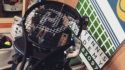 Black tennis racquet on top of restringing machine with poster in background