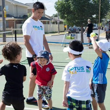 Male tennis coach teaching four young students, one smiling and one hold a green tennis ball