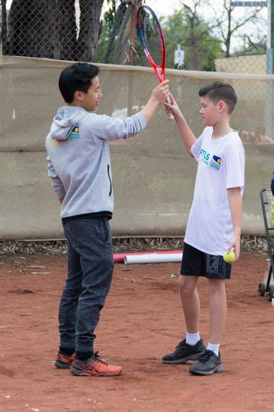 Male tennis coach teaching young male student how to hold tennis racquet standing on clay court