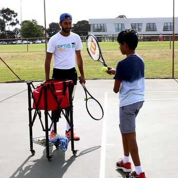 Tennis coach conducting private tennis lessons to kid