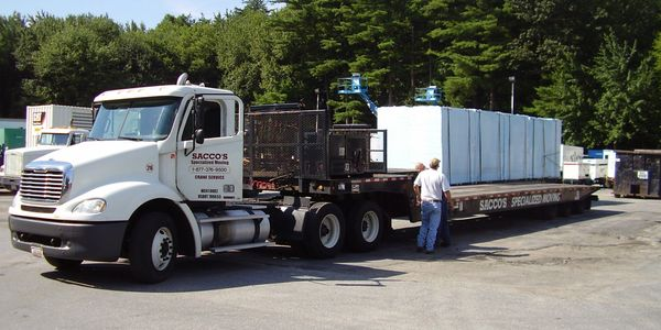 tractor-trailer truck with a low-bed trailer hauling equipment