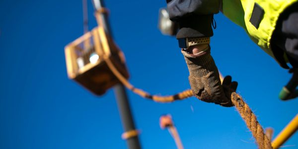 Rigger using a crane to hoist valuable machinery