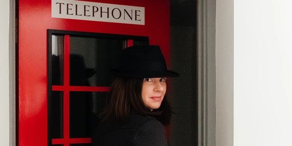 Fiona Lomas, Founder & Director of The Brand Detectives, in detective-themed disguise entering a telephone box door looking back to the camera.