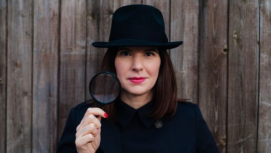 Fiona Lomas, Founder & Director of The Brand Detectives, shown wearing detective-themed outfit with a magnifying glass held up.