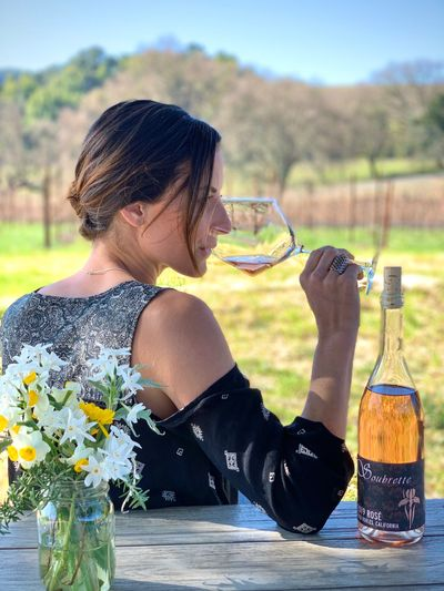 A woman drinking rose wine in a vineyard.