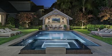 Timber frame pool pavilion beyond rectangular pool & hottub with bluestone & black glass liner tile