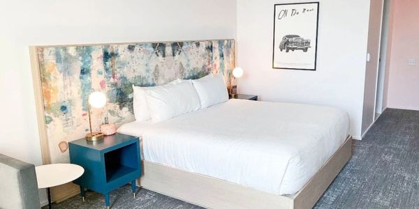 Birch bed with painted upholstery board, & blue open faced side tables in the Quirk Charlottesville