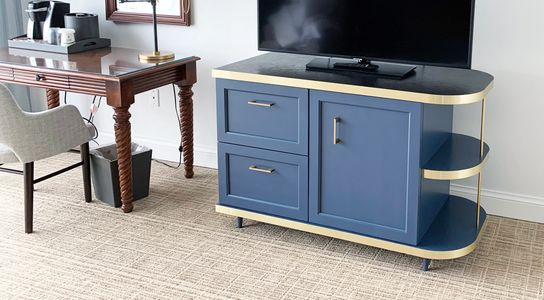 Blue and gold accent entertainment center with curved rounded edge and shaker style cabinet doors.