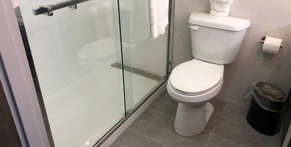 After picture with bathtub to shower conversion, gray floor tile and glass sliding shower door.
