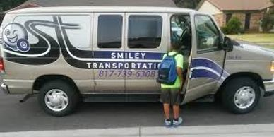 A student getting on the Smiley Transportation shuttle heading  to school.