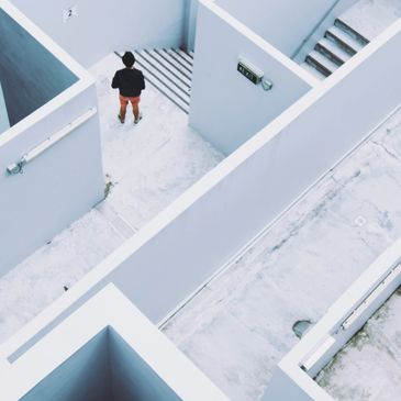 Man stands in middle of a maze of staircases and walls