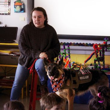 A girl holds the leash to her service dog as she talks to a class full of students