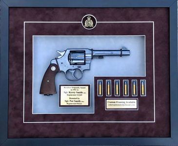 RCMP revolver in custom framed display with bullets.