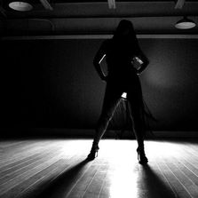 dancer in silhouette standing on a dance floor