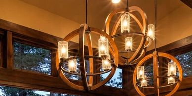 Large wood and iron pendant lighting for mountain home design done by The Design Gallery