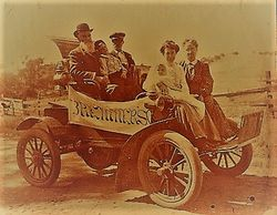 "Bremner family in the early 1900s riding a horseless carriage with a banner advertising ""Bremners."""