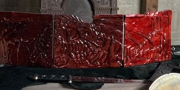A red, carved-wood DM screen with a dracolich on it.  It sits on a table near an axe.