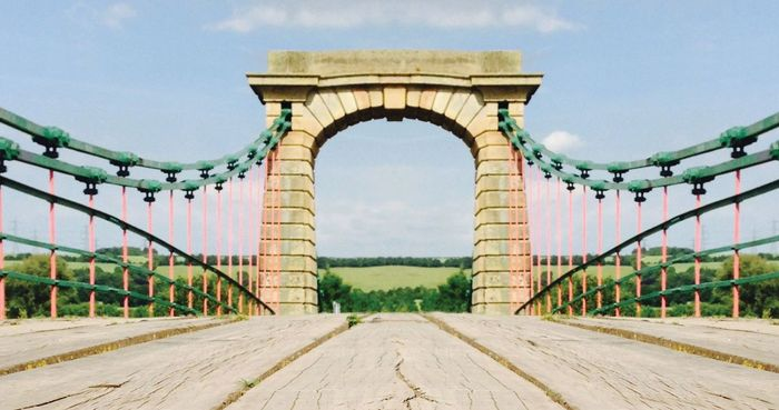 Entrance to antique suspension foot bridge with stone arch in center.