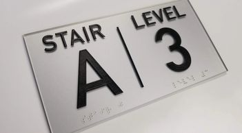 ADA compliant stair signage with raised text and braille for fire code and occupancy of a building.