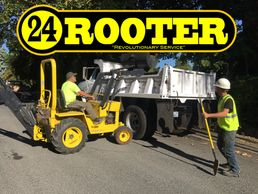 24 rooter yakima plumbers excavating at a plumbing job site with backhoe and dump truck