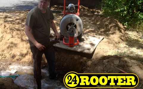 Yakima plumber from 24 rooter working on a sewer drain removing roots with a sewer cleaning machine